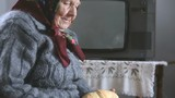 Old grandmother sniffing bread
