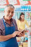 Supermarket clerk using a tablet