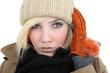 blonde junge Frau mit Mütze und Handschuhen