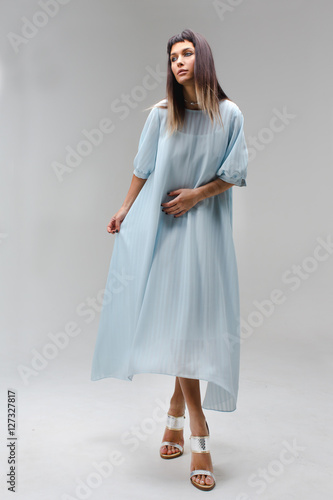 Plakát, Obraz Woman make step in light long blue dress in studio