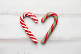 Peppermint candy cane heart on white wooden background - 127350058