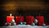 Weihnachtsschmuck und 4 Kerzen von denen eine symbolisch für den 1. Advent leuchtet