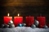 Weihnachtsschmuck und 4 Kerzen von denen zwei symbolisch für den 2. Advent leuchten
