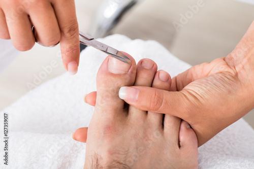 Fotobehang Pedicure Manicurist With Scissors Trimming Person's Toenail
