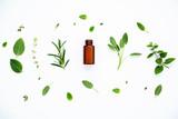 Bottle of essential oil with fresh herbal sage, rosemary, lemon - 127376425