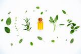 Bottle of essential oil with fresh herbal sage, rosemary, lemon - 127376448