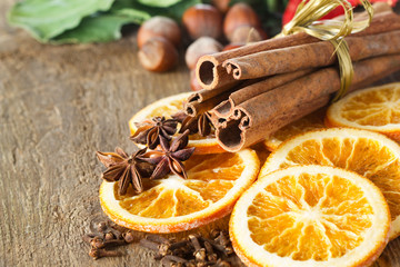 cinnamon sticks, nuts and dried orange slices on wooden background