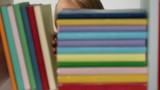 Little girl arranging books on bookshelf