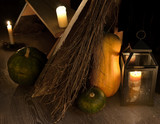 Scary occult still life with witch broomstick, pumpkins and candles by staircase