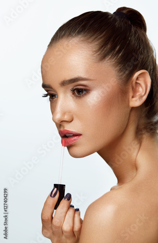 Poster Beautiful Woman Doing Makeup Using Lip Gloss On Lips. Cosmetics