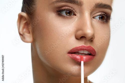 Poster Beautiful Woman Doing Makeup Using Lip Gloss On Lips. Cosmetics