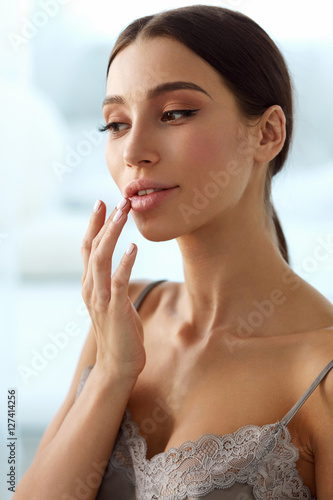 Lips Skin Care. Woman With Beauty Face Applying Lip Balm On Poster