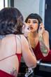 Frau in rückenfreiem Abendkleid macht sich mit Make-up ausgehfertig
