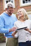 Mature Couple Standing Outside House Looking At Property Details