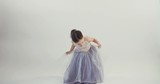 Little girl wearing a dress dancing on a white background studio