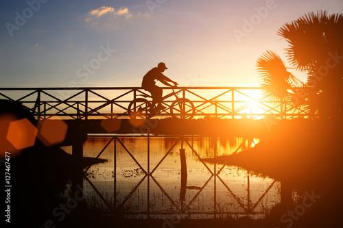 Foto op Plexiglas Bruin biker riding bicycle on the bridge
