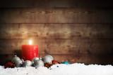 Weihnachtsschmuck und eine brennende Adventskerze