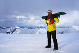 Snowboarder carries a snowboard in hand.