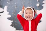 Очень веселый ребенок в рождественском костюме на новогоднем фоне