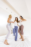 Girls friends jumping on bed