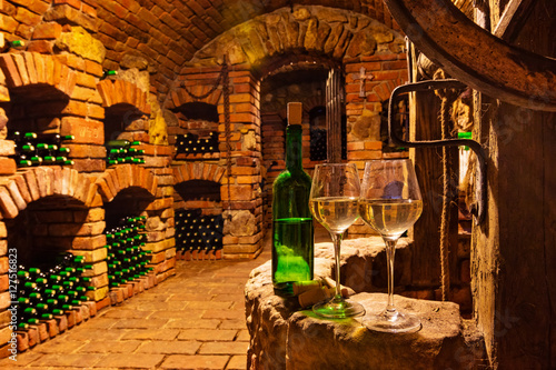 Fototapeta Small wine cellar with bottle and glasses of wine
