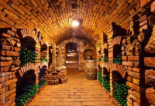 Fototapeta Small wine cellar with bottles and keg