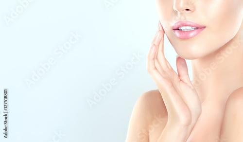 Leinwanddruck Bild Beautiful Young Woman with clean fresh skin  touch  face . Facial  treatment  , cosmetology , beauty  and spa .