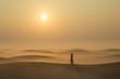 a woman in a desert at sunrise near Dubai