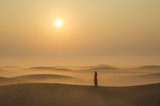 a woman in a desert at sunrise near Dubai