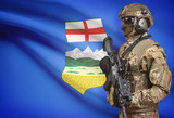 Soldier in helmet holding machine gun with Canadian province flag on background series - Alberta