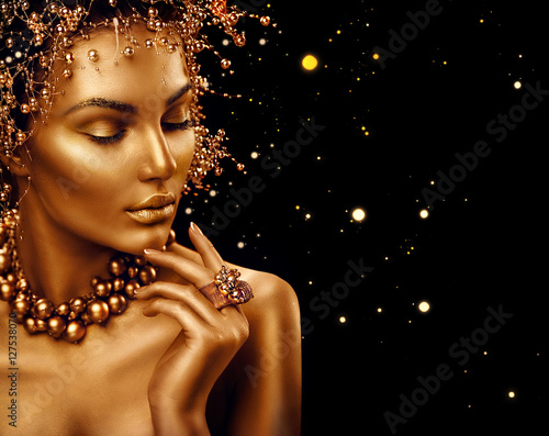 Beauty fashion model girl with golden skin, makeup and hairstyle isolated on black background