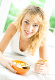 Portrait of young smiling woman eating muesli or cornflakes, indoors