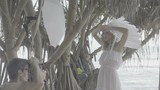 Beautiful model wearing white eye lenses, dress and indian feather hat posing for male photographer during outdoor photo shoot - video in slow motion