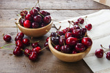 Two wooden bowls of delicious cherries