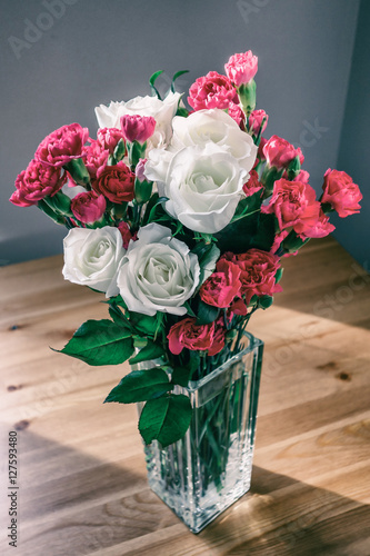 Bouquet of white roses and cloves in glass vase Plakát