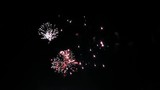 Colorful fireworks in the night sky. Red, blue and green flashes. Clouds of smoke.