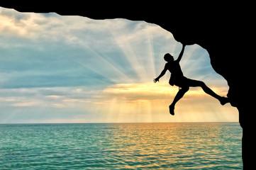 Mountaineer climbs cliff over sea sunset