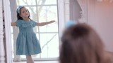 little girl in blue dress looking in the mirror and admiring herself