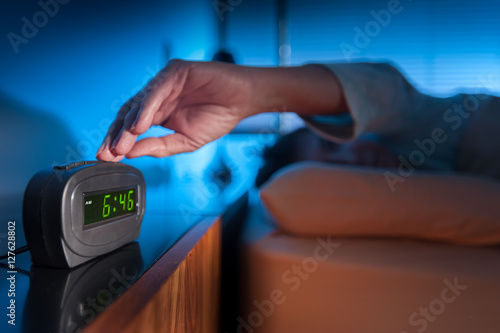 Poster Woman pressing snooze button on early morning digital alarm clock