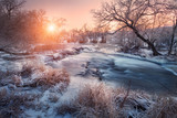 Christmas background with snowy forest. Winter landscape with snowy trees, beautiful frozen river and bushes at sunset. Winter forest. Colorful sky. Water in motion. Trees covered with snow and ice