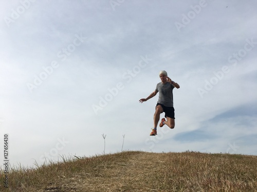Zdjęcia na płótnie, fototapety, obrazy : Man running fast downhill on grassy bank