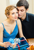 Young happy smiling amorous couple with gift and champagne at home. Love, relations, romantic concept shot.