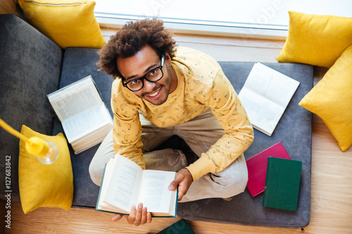 Poszter Happy african american young man sitting and studying at home