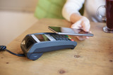 Woman uses smart phone for wireless pay in the cafe