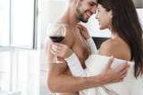Cheerful couple hugging and drinking red wine at home