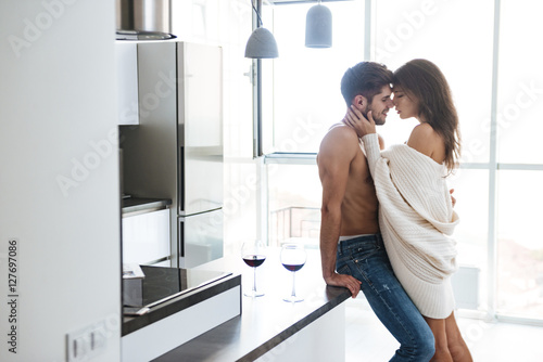 Plakat Sexy couple standing and hugging on the kitchen
