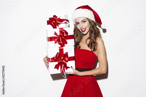 Poster Happy young woman in santa claus costume with gift boxes