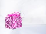 Pink gift box on gentle fabrics background