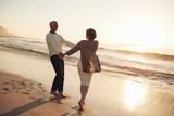 Fototapety Romantic mature couple enjoying a day at the beach