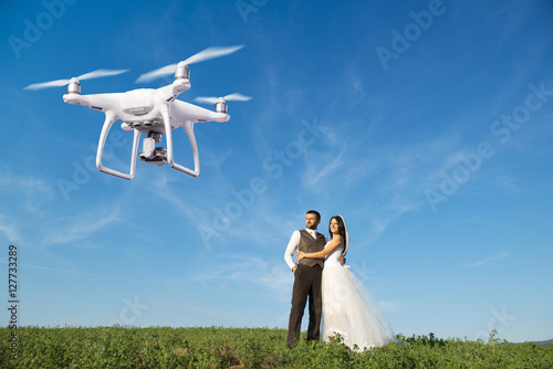 Juliste Hovering drone taking pictures of wedding couple in nature